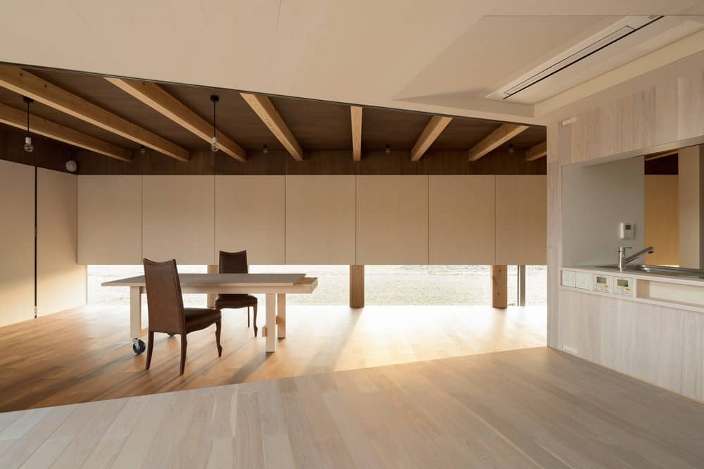 This area by the kitchen is fitted with a large wooden rectagular dining table that matches the tone of the walls that make it stand out against the the dark hardwood flooring.