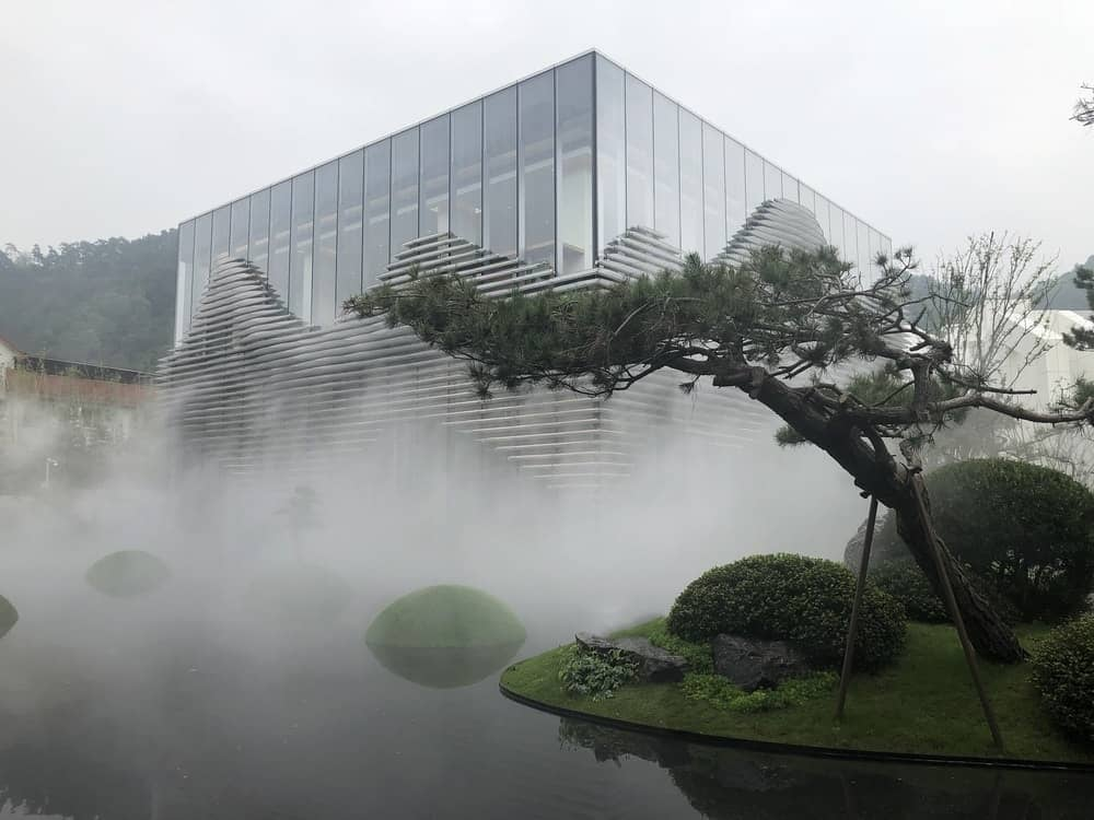 This is a look at the glass building with a thick fog covering the water scenery and landscape.