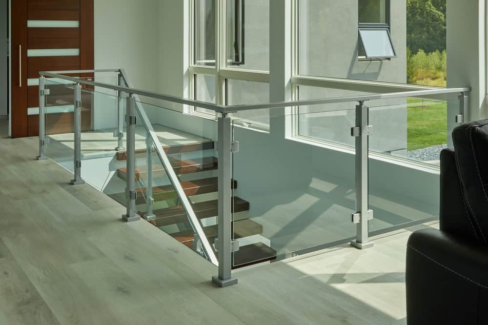 This is a closer look at the top-floor landing with the staircase leading to a small indoor balcony of glass railings.