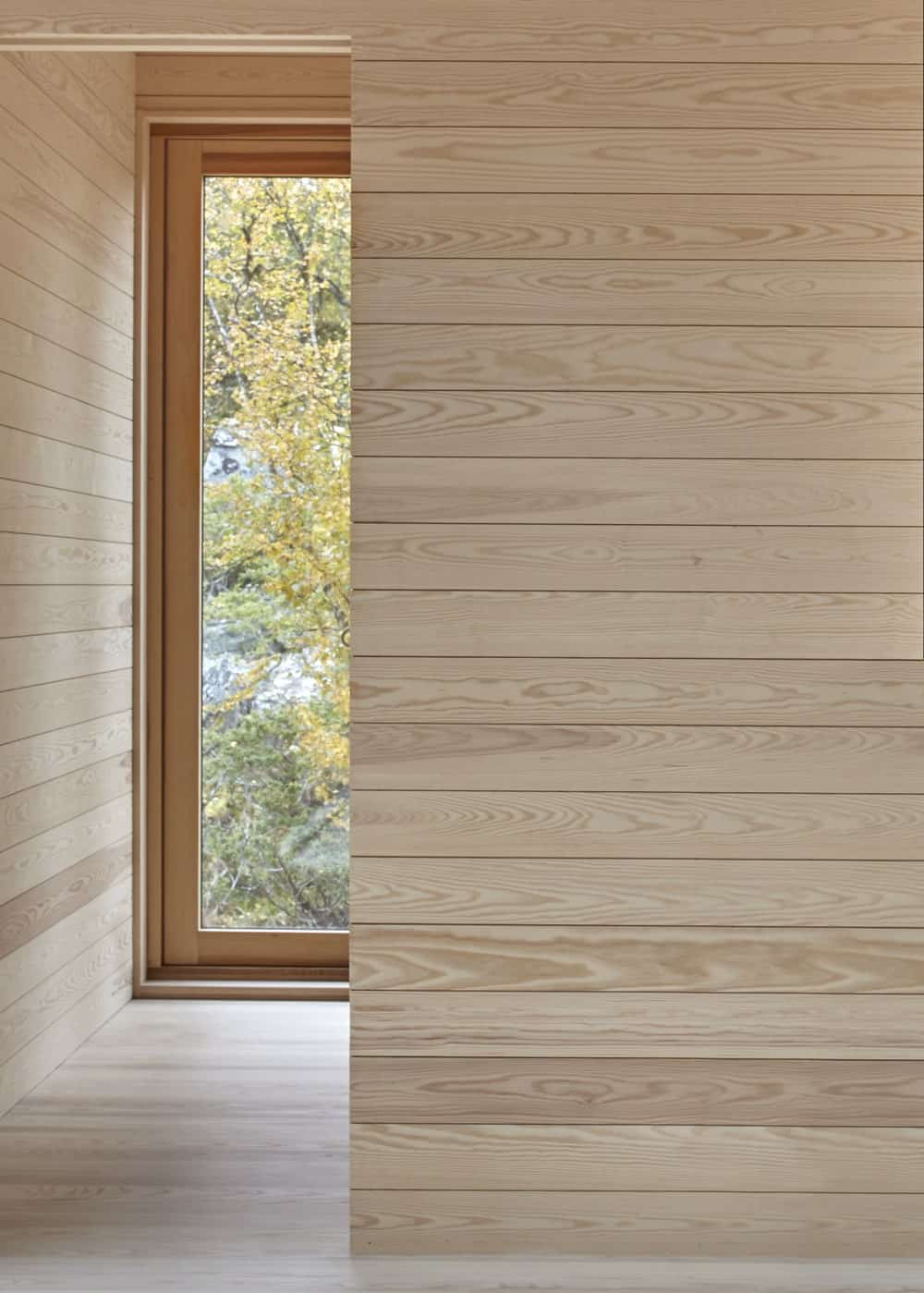 The light tone of the shiplap walls of the interiors of the house are further brightened by the abundance of natural light that goes in from the glass walls.