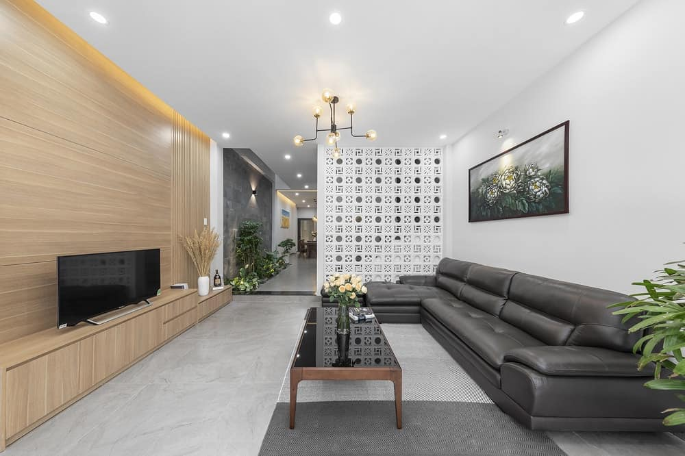 This is a view of the living room with a large black leather L-shaped sectional sofa that is paired with a black glass-top coffee table and a TV on a wooden entertainment cabinet built into the wooden wall.