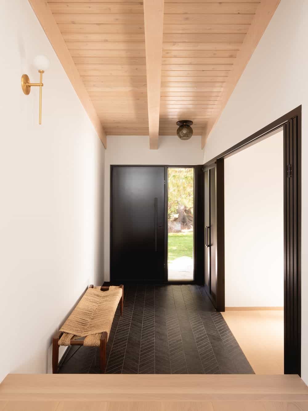 Upon entry of the house, you are welcomed by this simple foyer that has a bench on the side. It stands out against the dark hardwood flooring that matches with the main door.