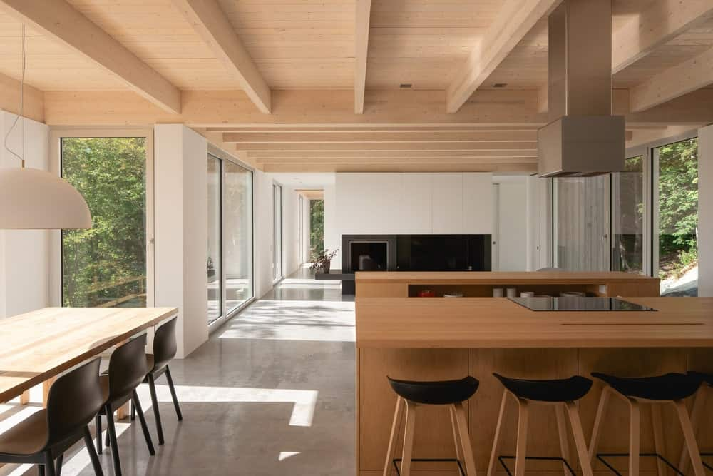 This is the close look at the kitchen with a wooden kitchen island paired with stools that have black seats.