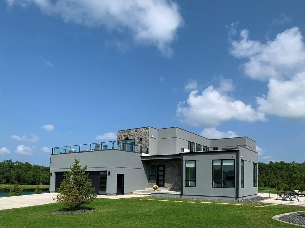 This is a view of the exterior of the house with its gray modern tone, large glass walls and windows and balconies.