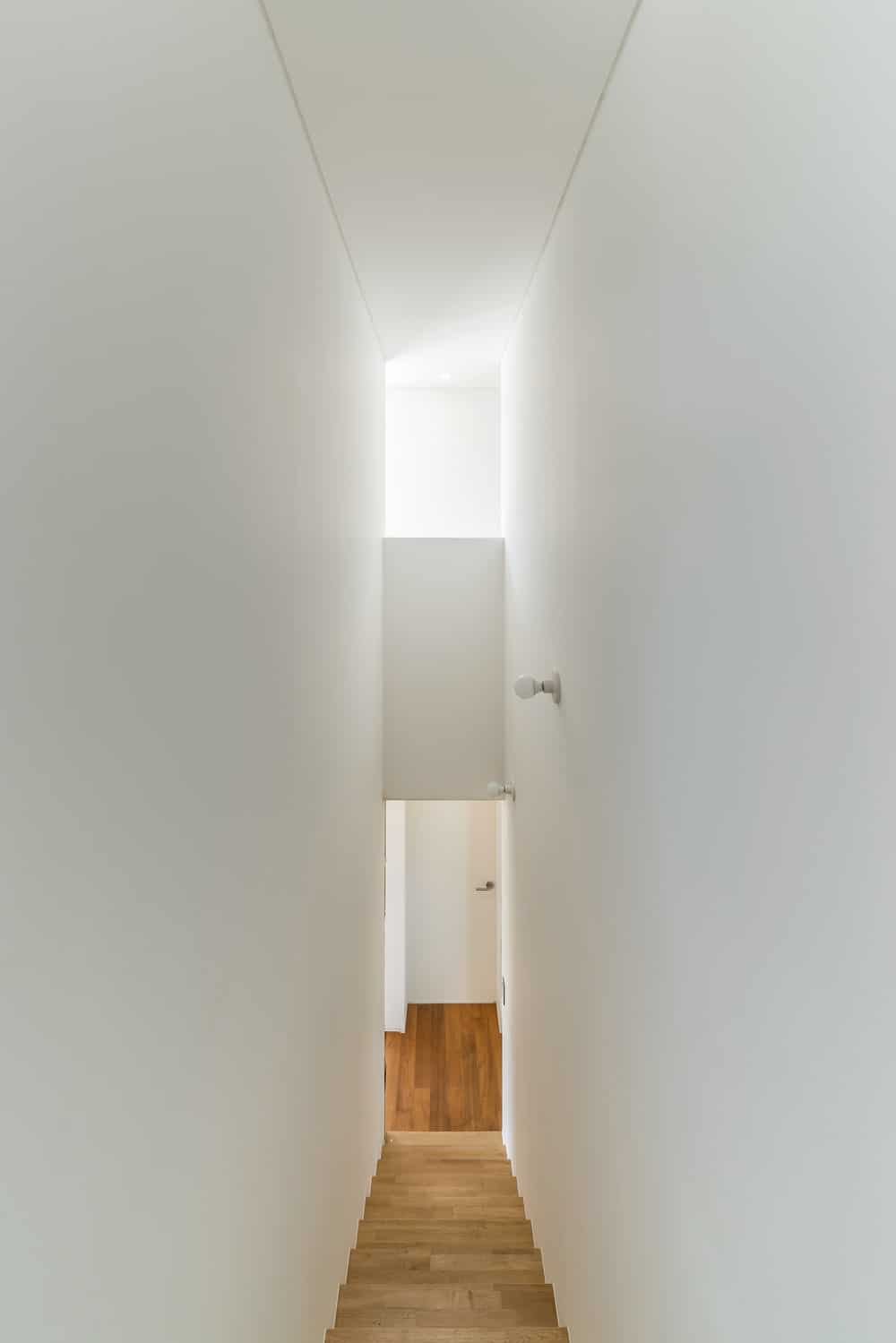 This is a look down the stairs that is lit with natural lighting from the transom window above.