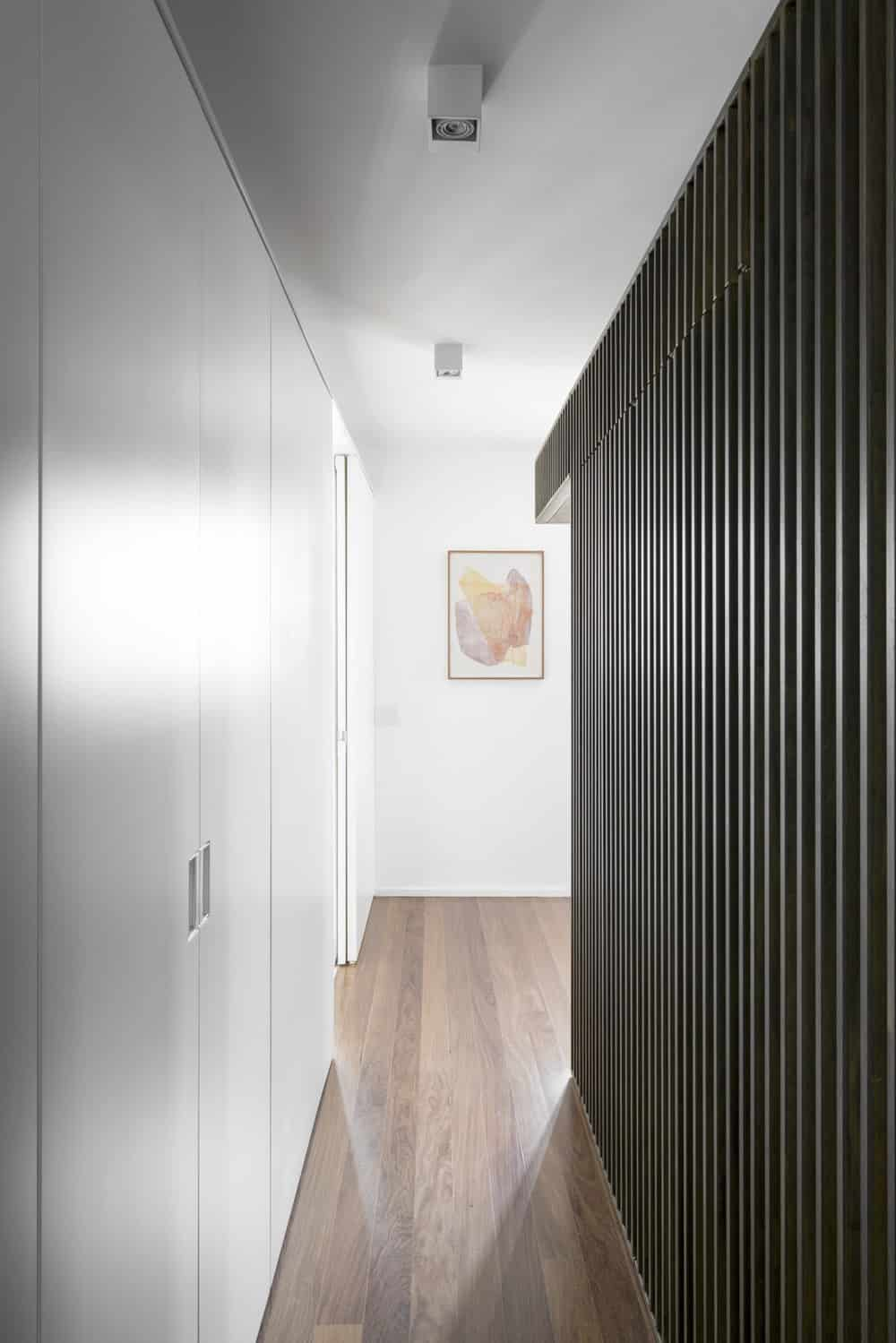 This is a hallway with white built-in cabinets on one side and dark wooden slats on the other.