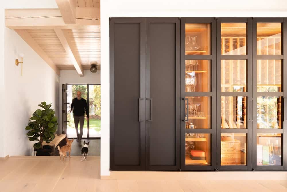 This view showcases more of the small and simple foyer and the large cabinet for crystal and silverware around the corner with a dark set of doors.