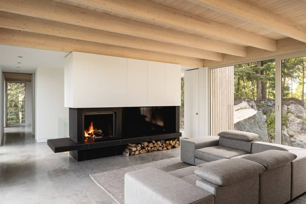 This is a close look at the living room with a large gray L-shaped sectional sofa facing a modern fireplace.