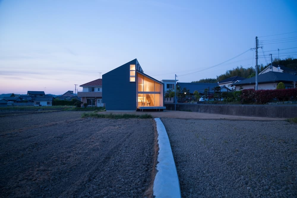 This si a nighttime view of the house from afar. This showcases the warm glow of the house glass walls and windows giving it a distinct look against the surrounding landscape.