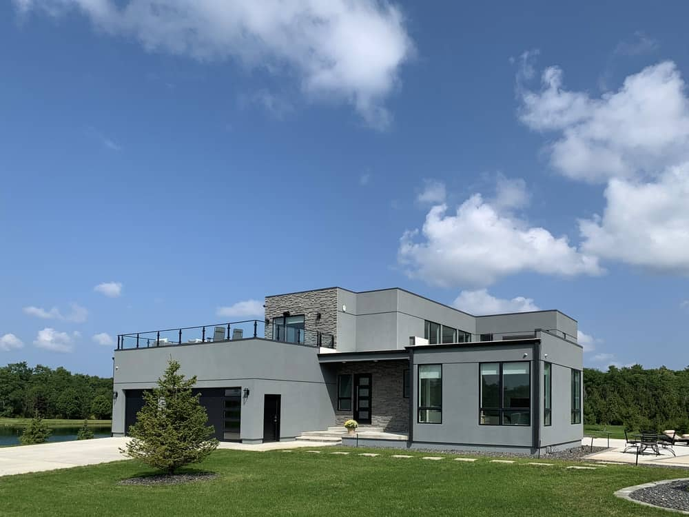 The modern gray tones of the house is complemented by the lush landscaping that surrounds it with grass lawns and trees.