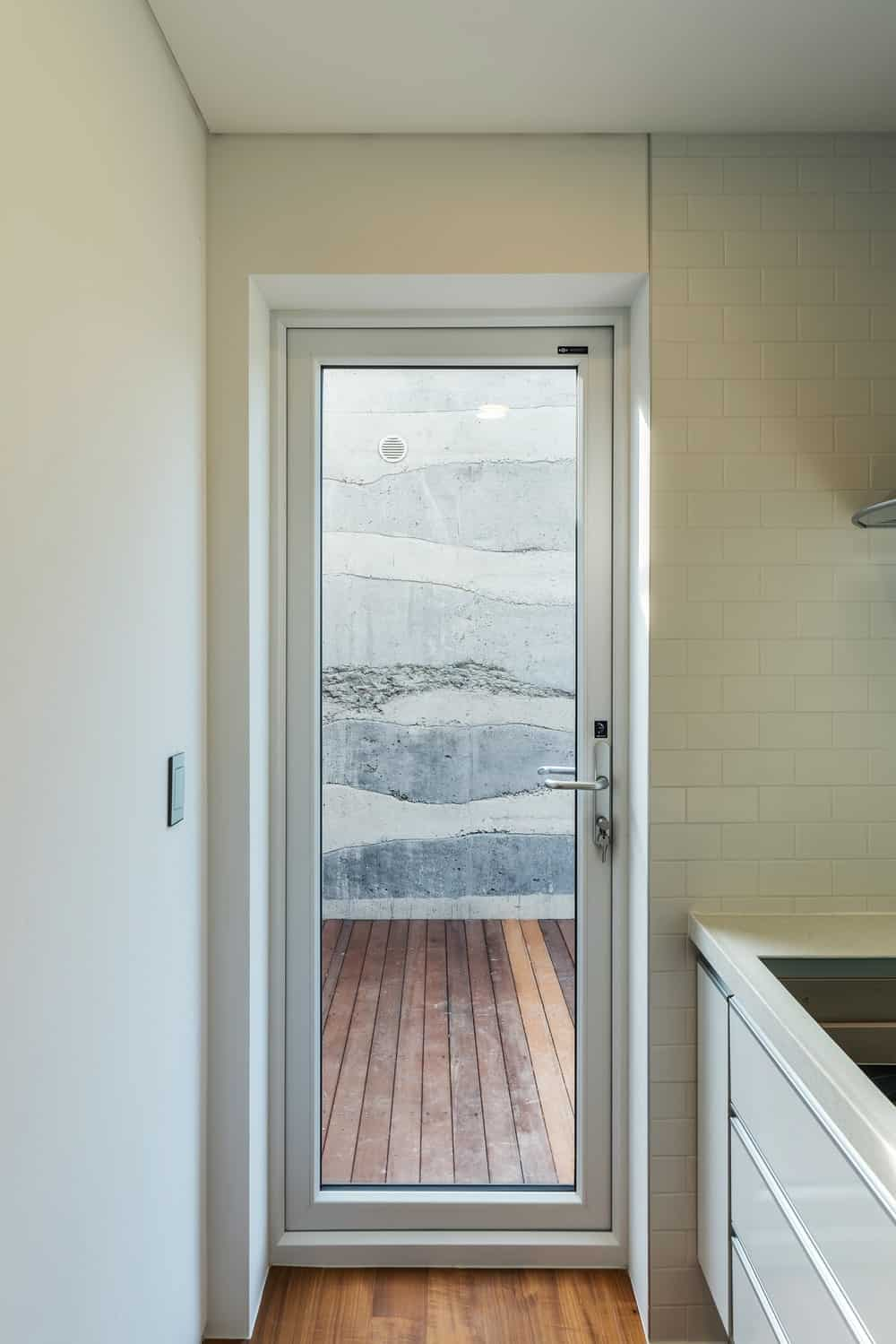 This is a close look at the glass door of the kitchen that leads to a wooden walkway outside.