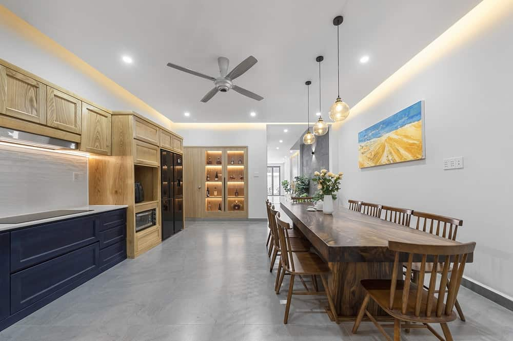 This is the spacious dining area and kitchen that has a large wooden dining set that is spaced across from the cabinetry of the kitchen on the opposite wall.