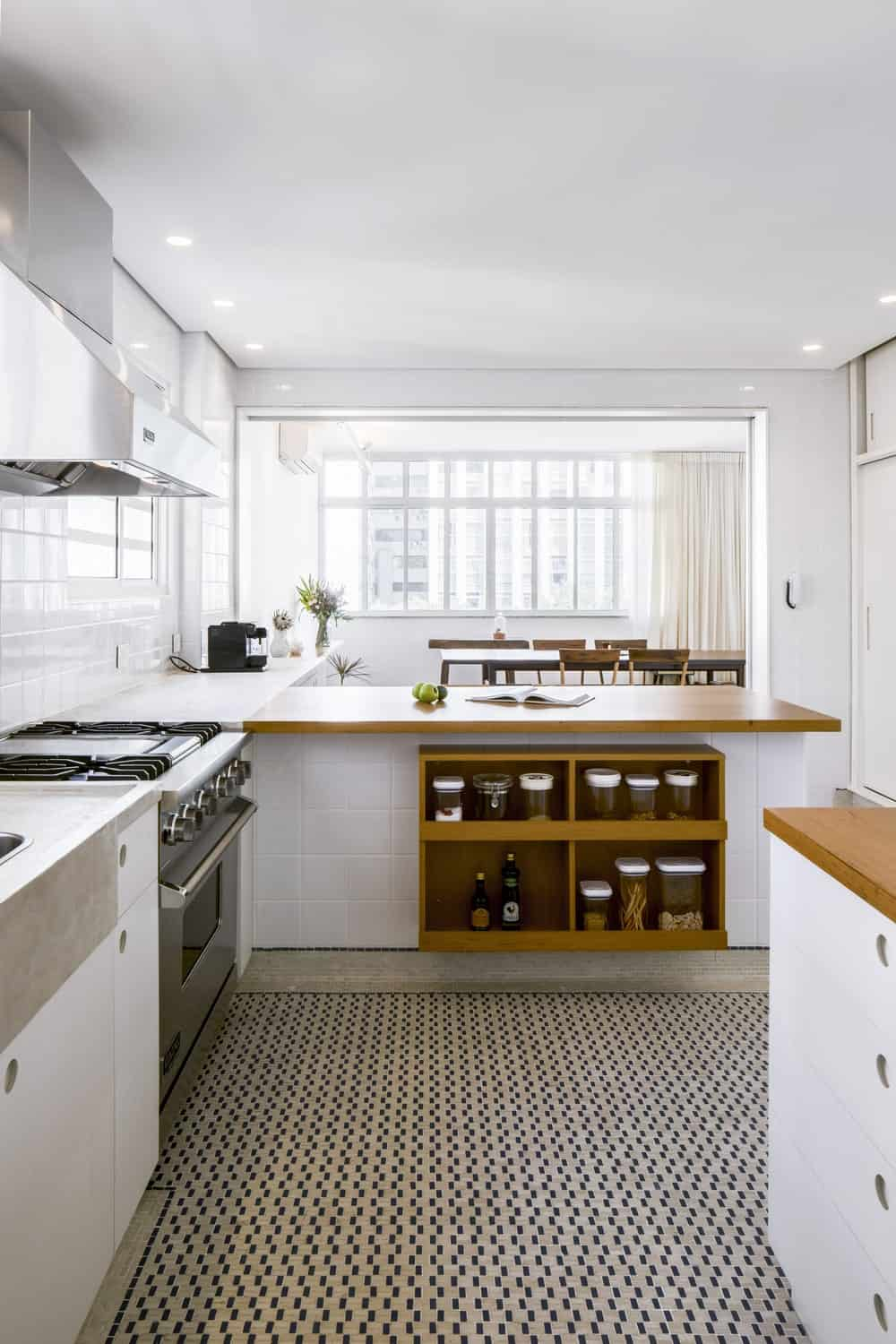 This is a look at the other side of the kitchen peninsula with built-in shelves that match the tone of the woodtop counters complemented by the bright white tones.