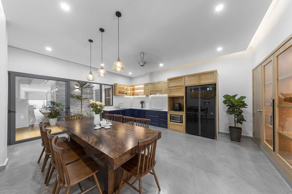 This angle of the room showcases more of the kitchen cabinetry on the far side. It has light wooden tones that is contrasted by the dark blue cabinetry at the bottom and the black appliances.