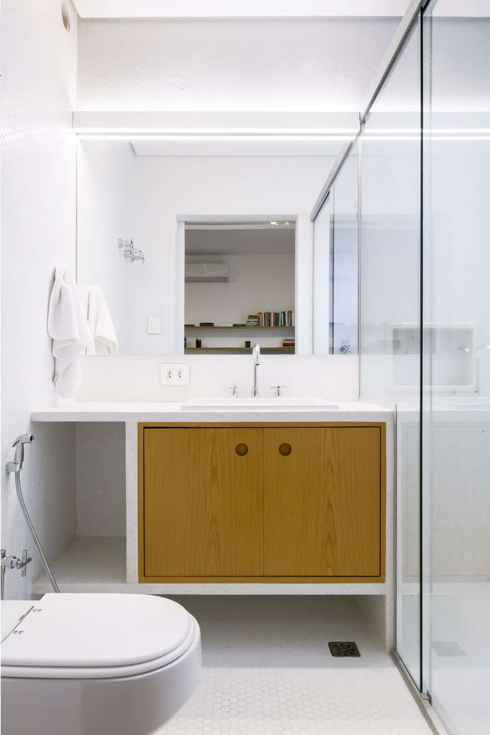 This bathroom has a simple modern vanity with a couple of wooden cabinets next to the toilet and the glass-enclosed shower area.