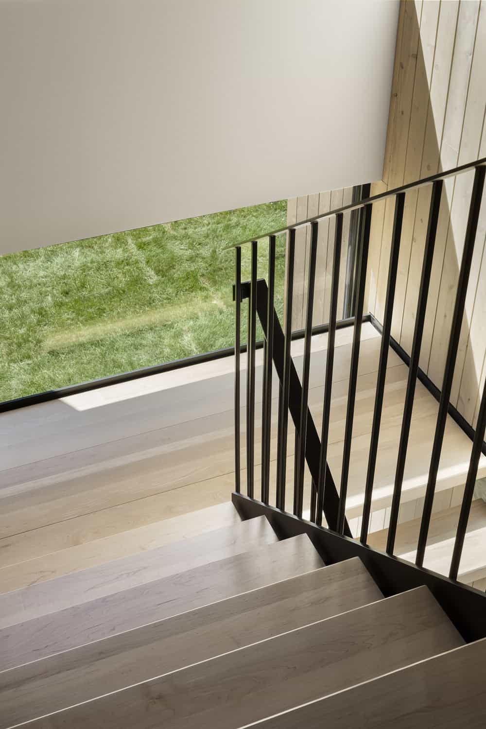 This is an angled look at the staircase showcasing more of its light wooden steps and contrasting black wrought iron railings.