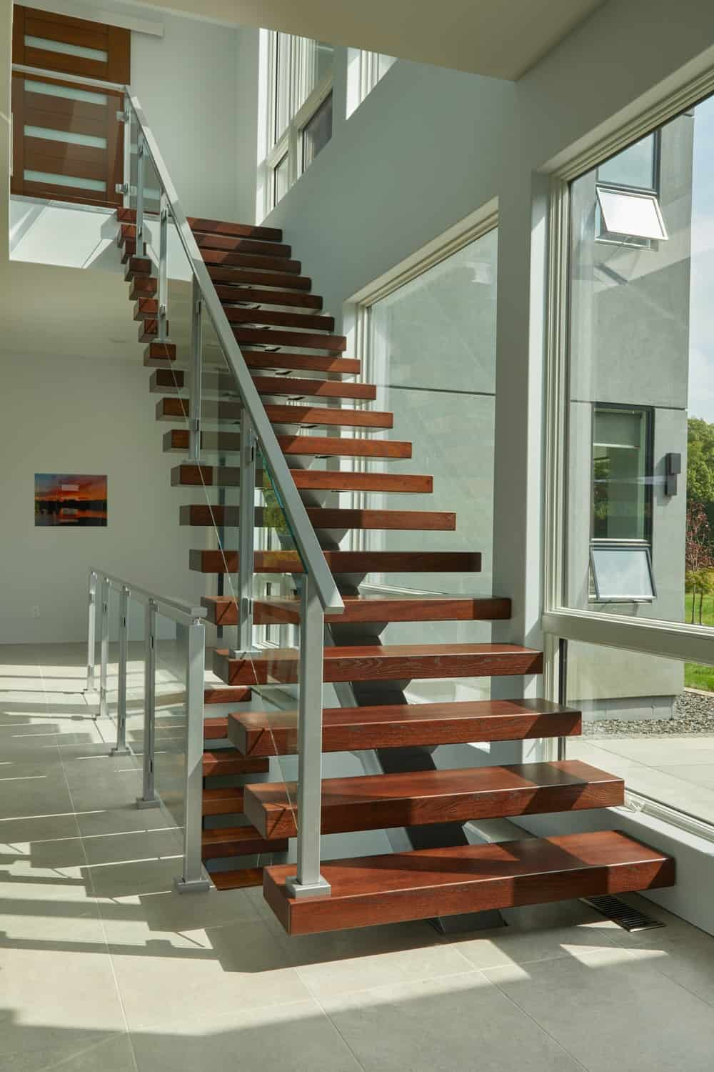 The staircase is illuminated by the natural lighting of the glass walls on its side.