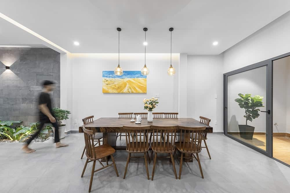 Across from the cabinetry of the kitchen is this dining area that has a wooden dining set that stands out against the gray concrete flooring.