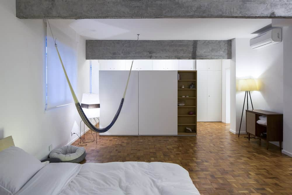 This is the bedroom with a white bed at the corner across from the large white cabinet on the far side with built-in shelves. These white elements are then complemented by the dark flooring.