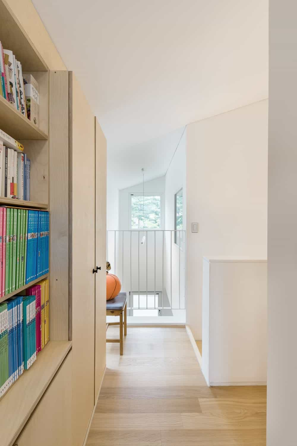 This is the library of the house with a alrge wooden built-in bookshelf lining the wall with cabinets on the far side matching the tone of the light hardwood flooring.