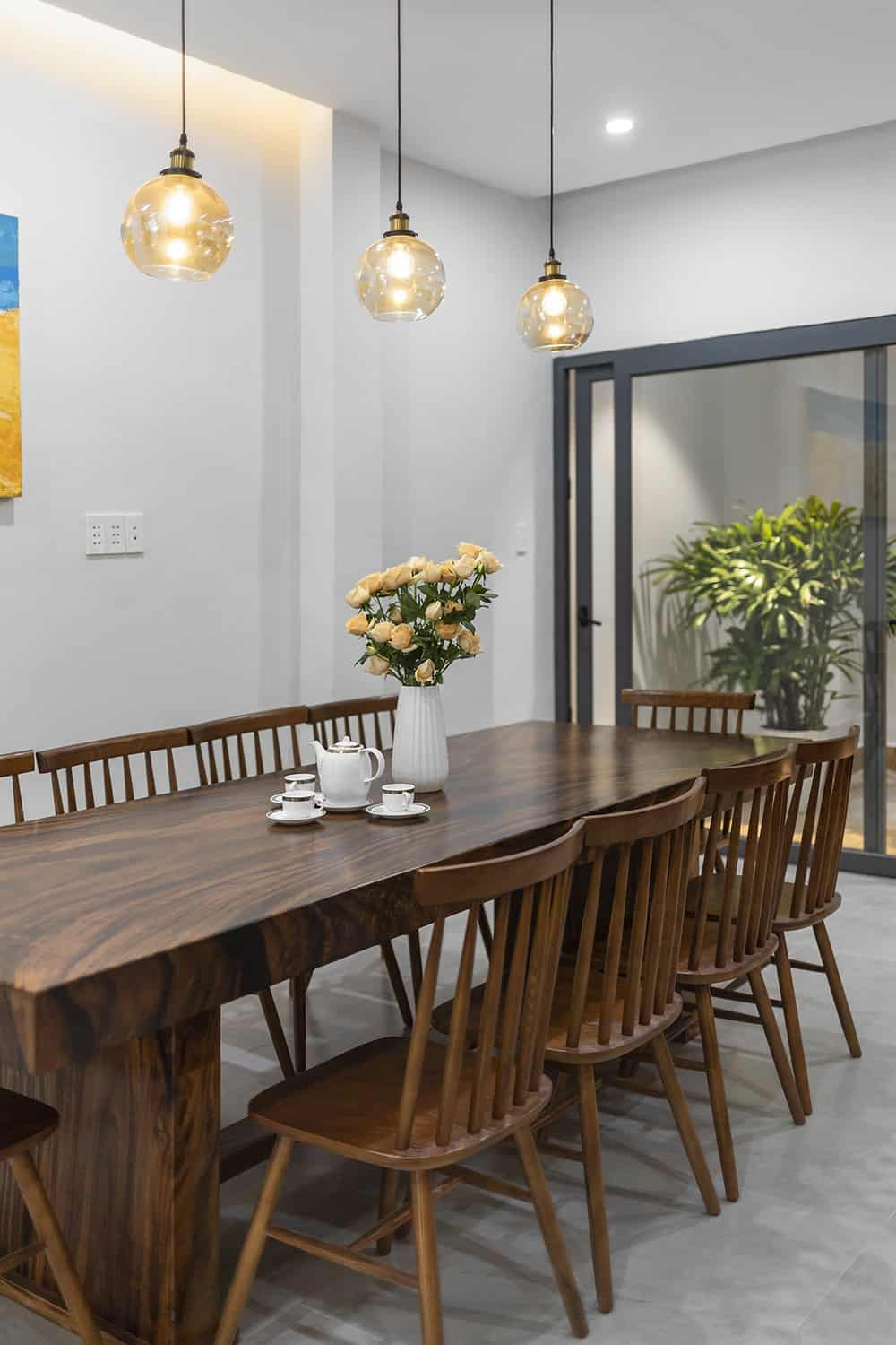 The large rectangular wooden dining table is surrounded by matching wooden chairs and topped with a row of three pendant lights.