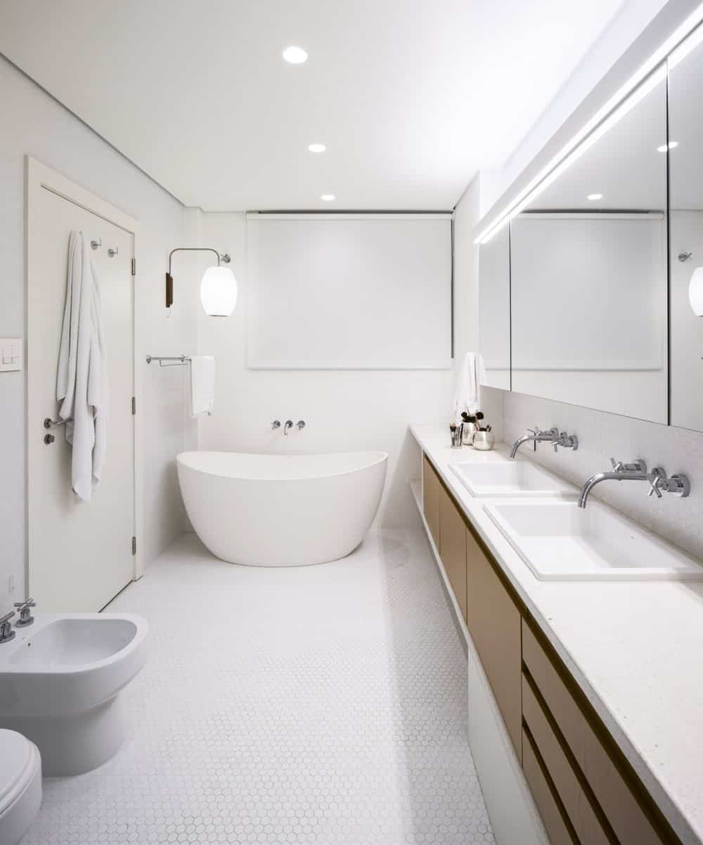 This bathroom has a freestanding bathtub at the far end beside the long and narrow two-sink vanity lining the wall.