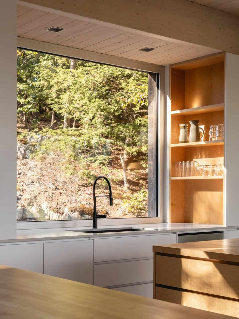 This is a close look at the faucet area of the kitchen that has white modern cabinetry illuminated by the large window.