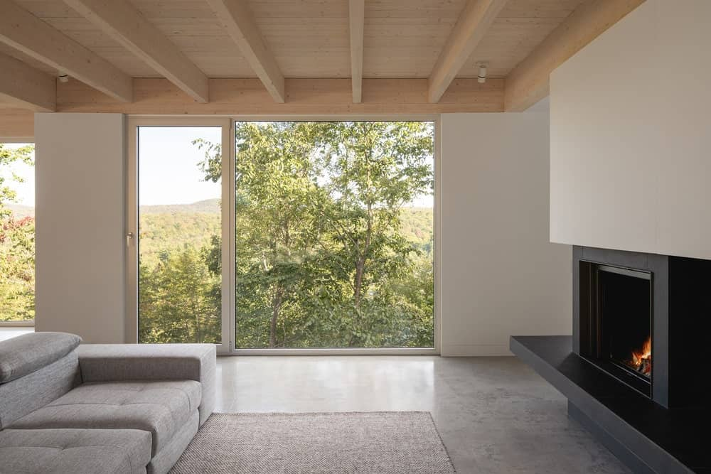 This is a look at the living room with a large glass wall on the far side that brings in natural lighting.