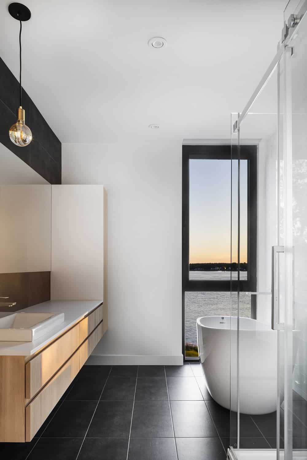 This bathroom has a glass-enclosed shower area, a freestanding bathtub at the far corner by the window and a floating wooden vanity with white countertop.