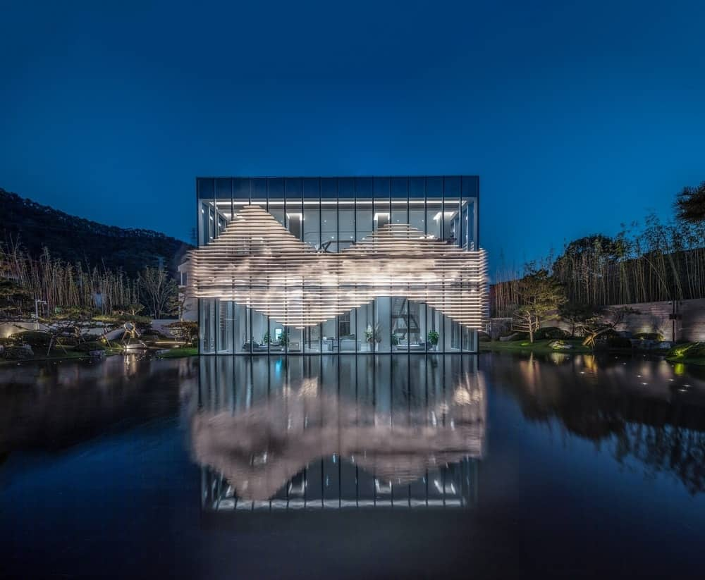 This is a farther view of the glass building showcasing the reflective pond that gives it a unique look.