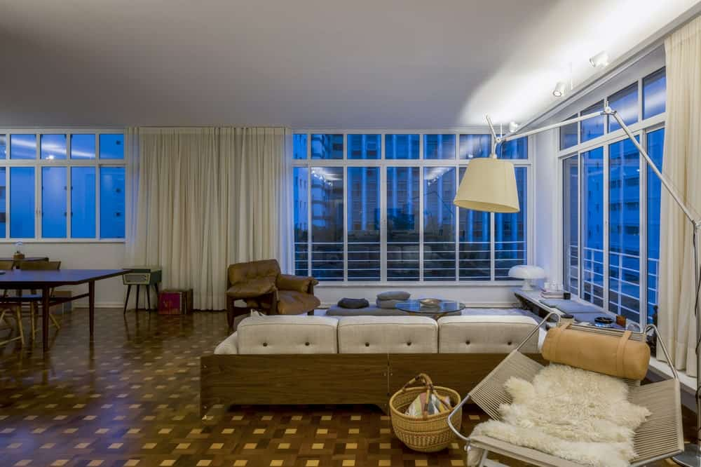 This is a nighttime view of the living room showing more of the sofa and the lights that are complemented by the dark view of the windows.