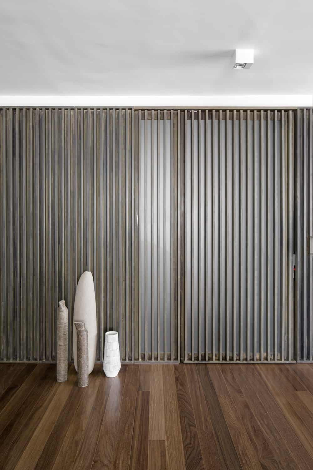 This is a close look at the slatted wall across from the sofa adorned with a few vases.
