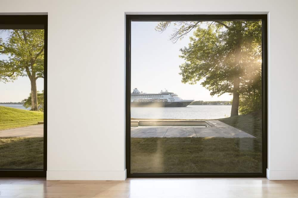 This great room has large glass walls that give a clear view of the water scenery beyond.