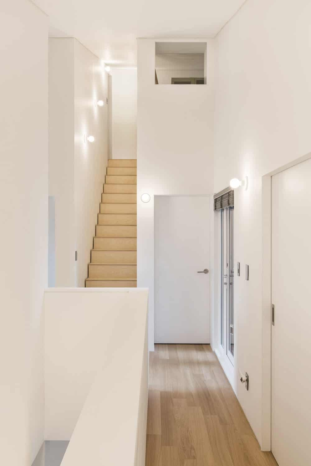 This is another angle of the indoor corridor that shows the staircase with light wooden steps.