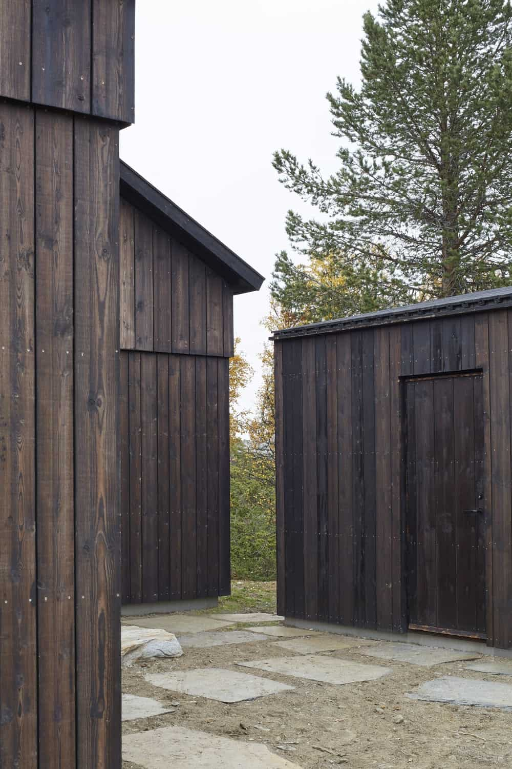 The structures of the house are consistent with its dark wooden tones and design as well as doors that blend with the walls.