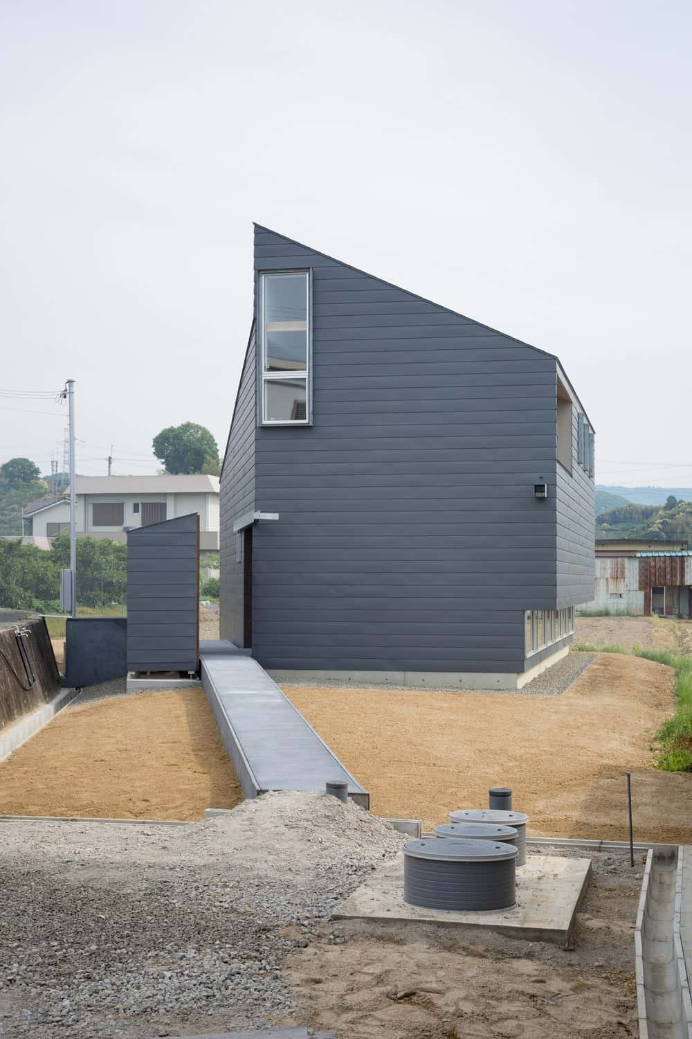 This is a view of the side elevation of the house showcasing more of the gray exterior walls paired with small windows.
