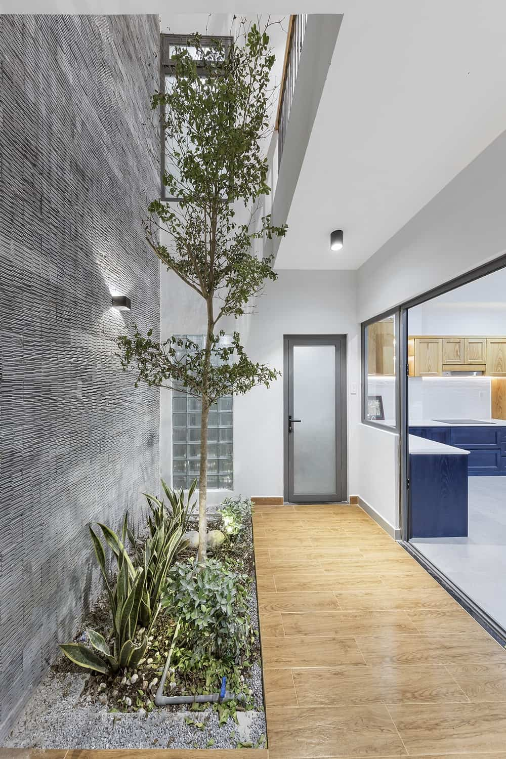 This is a look at the hallway on the side of the kitchen leading from the living room with a glass door, block glass panels, miniature garden on the side and a hardwood flooring that leads to the kitchen through glass doors.