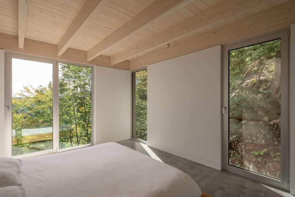 This is the simple bedroom with a large bed underneath a beamed ceiling with a wooden tone complemented by the green views outside the glass walls.