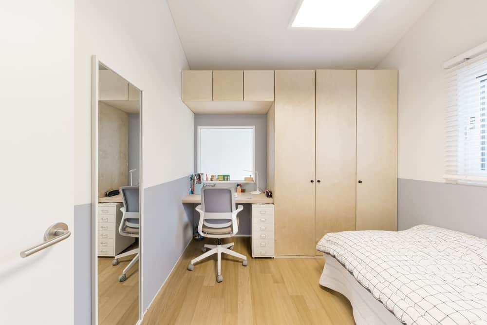 This is the kids room with a large bed across from the large wooden built-in structure that houses cabinets and a desk at the corner.