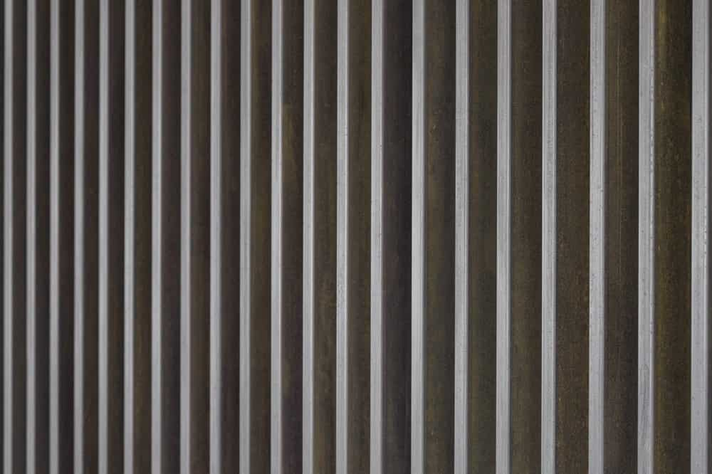The slatted wall has a consistent spacing that gives it a modern patterned look.
