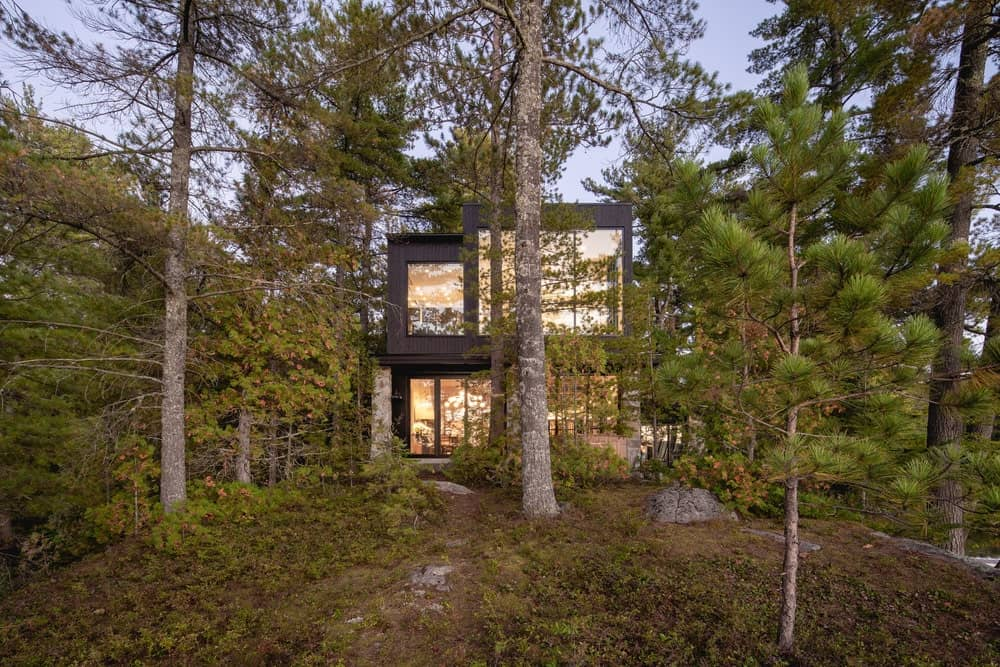 This other angle of the house showcases the warm glow of the glass walls and windows that makes the house stand out against the surrounding foliage of tall trees.