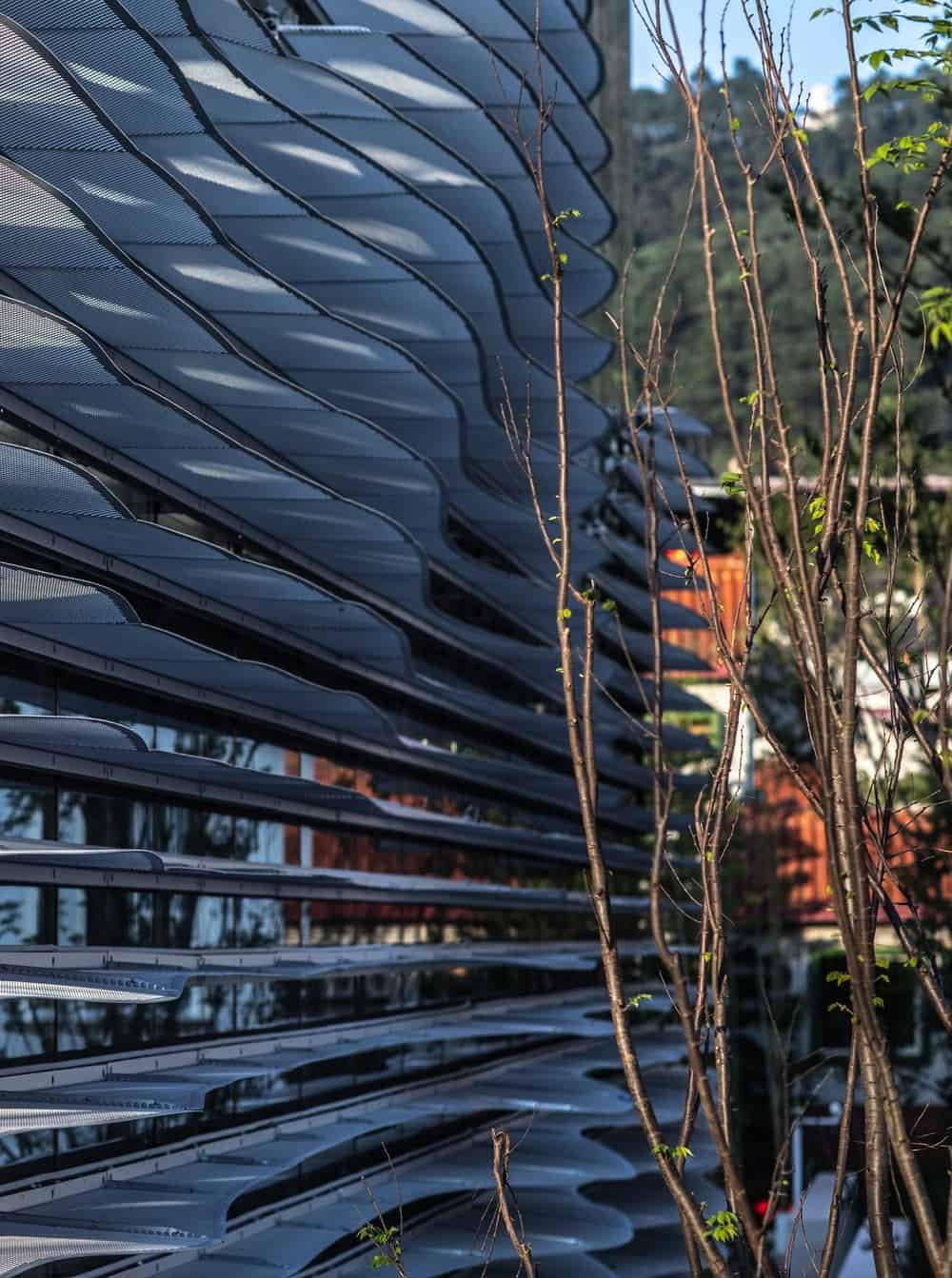 This is a close look at the structure attached to the glass walls of the building giving it a unique aesthetic that is complemented by the landscaping.