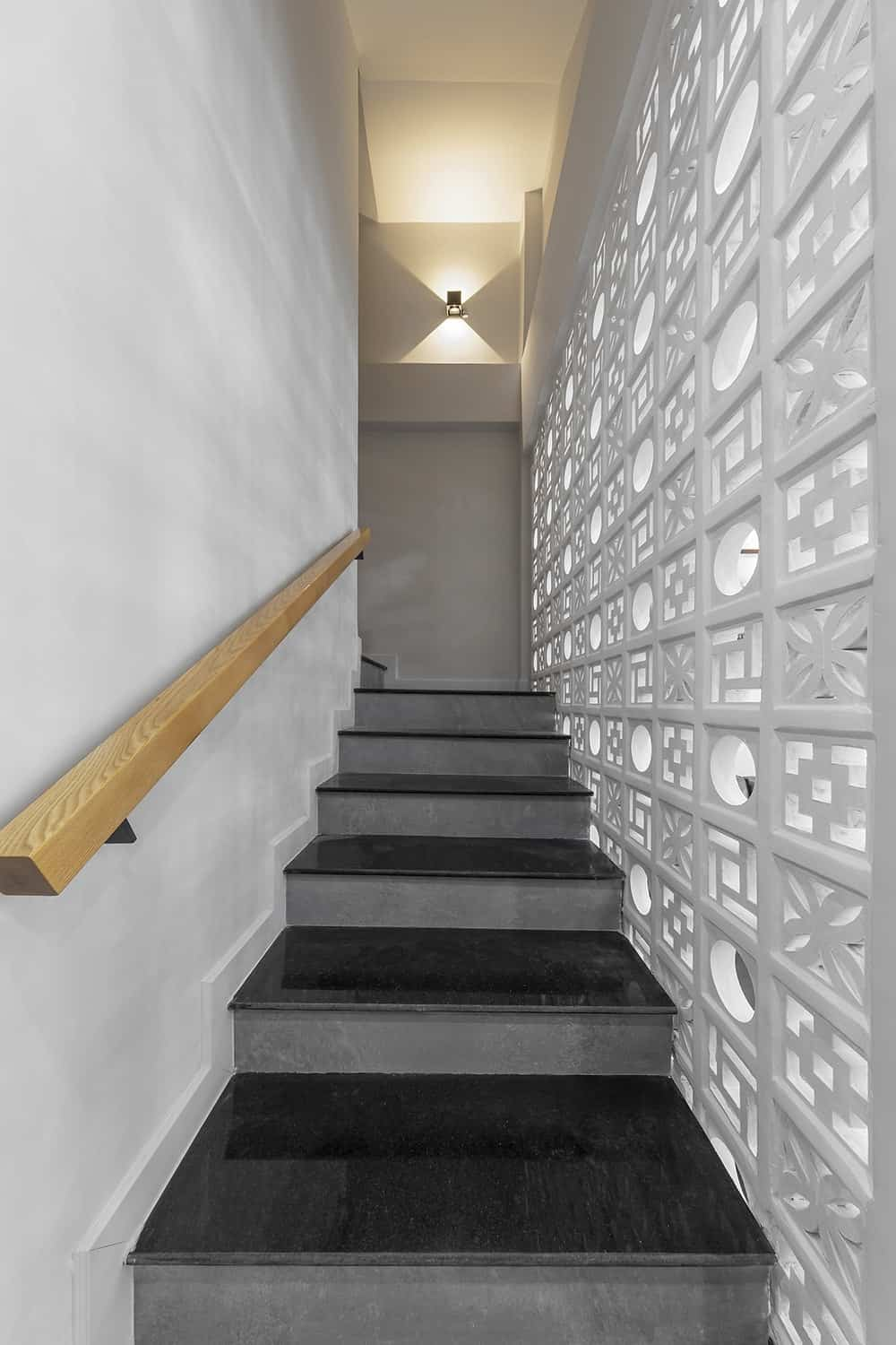 On the opposite side of the floating wooden hand rails is a gray wall with patterned decorative concrete blocks.
