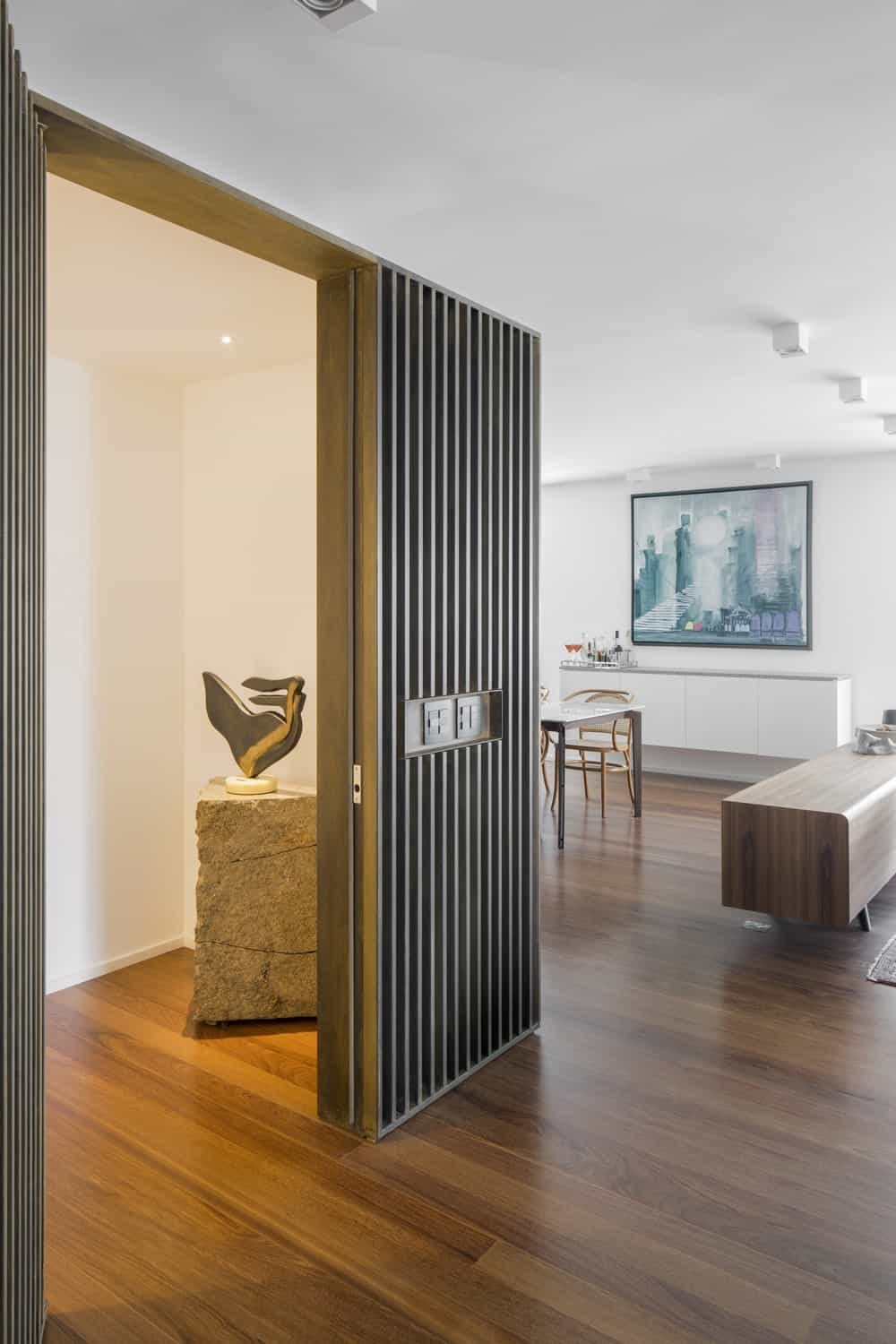 The slatted wall of the living room opens up to a hallway with warm lighting and a decoration sculpture.
