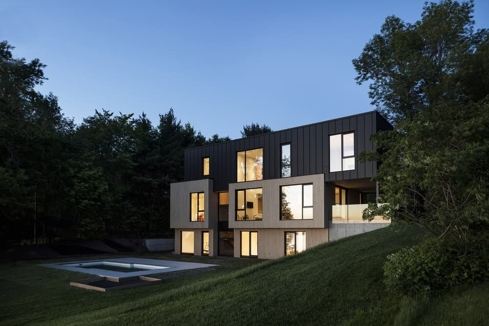 This is a nighttime view of the back of the house that showcases the warm glow of the windows making its stand out against the surrounding dark forest.