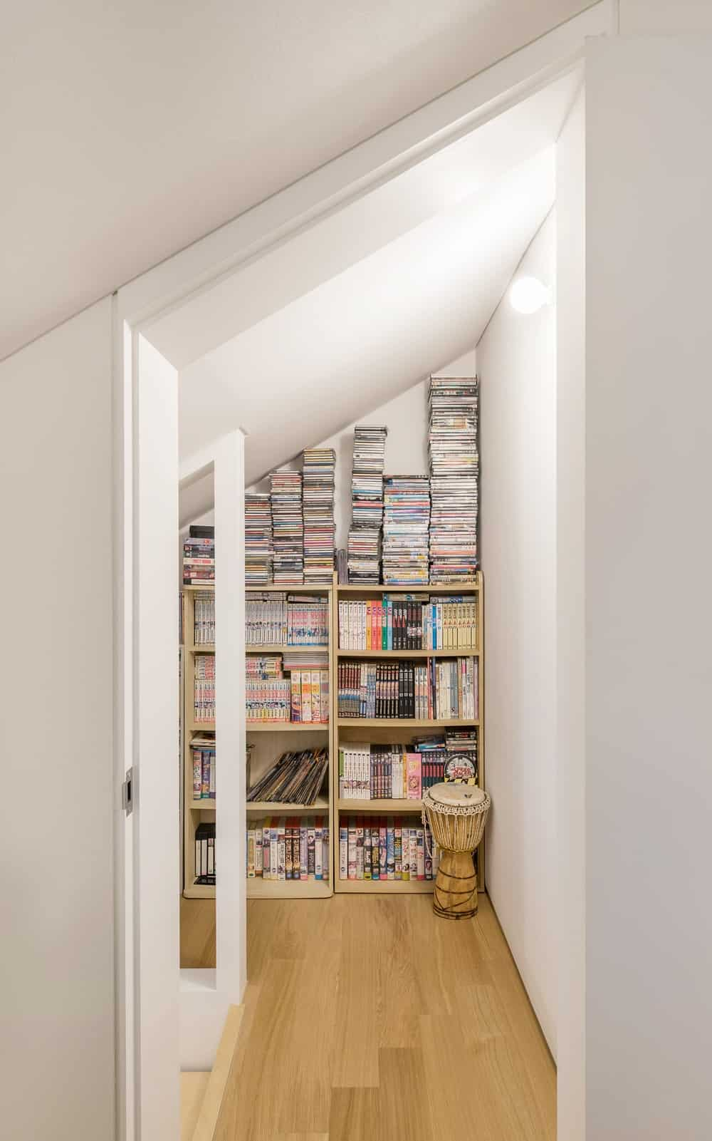 This is a view of the attic shoecasing the built-in bookshelves that makes the most out of the vertical space of the area.