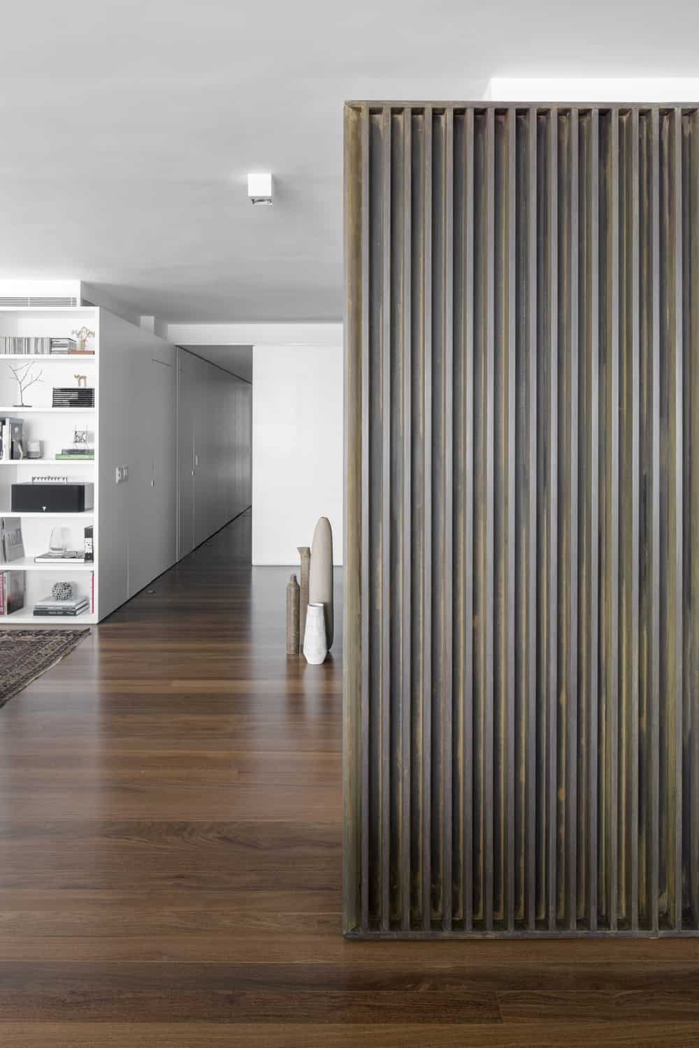 The dark wooden slatted wall that matches well with the dark hardwood flooring.