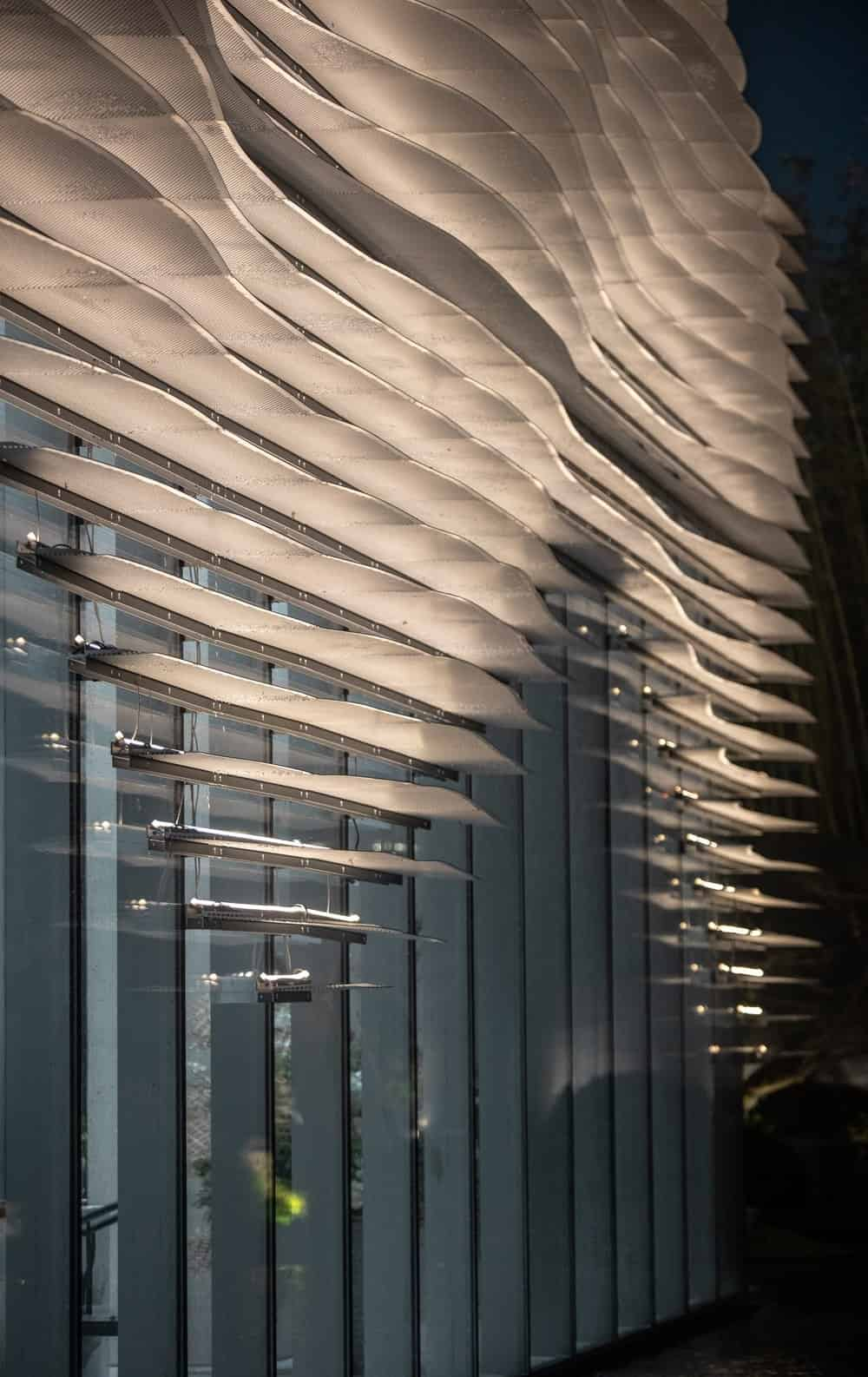 The exterior panels of the building lights up with a warm glow.