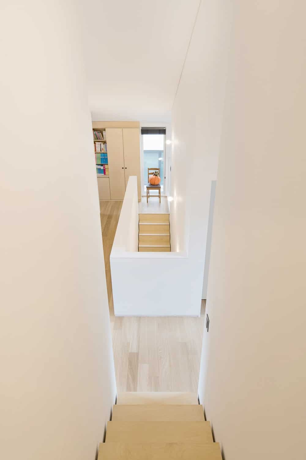 This is a look down the stairs that leads to the attic. this staircase is flanked with tall white walls on both sides.