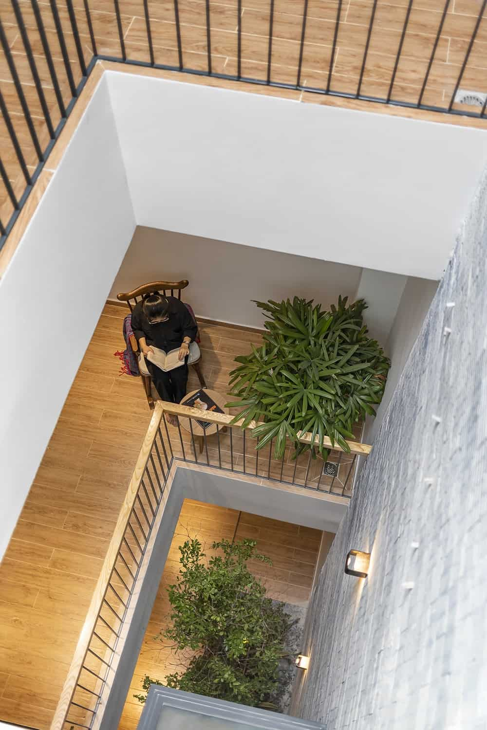 This is a look down the indoor balcony showcasing the potted plants that pair well with the hardwood flooring.